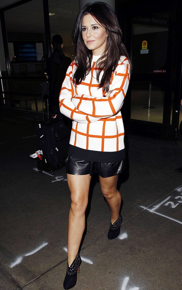 Dressed to impress: Cheryl looked chic in a black leather skirt, fierce spike-detail shoe boots and an orange and white checked sweater