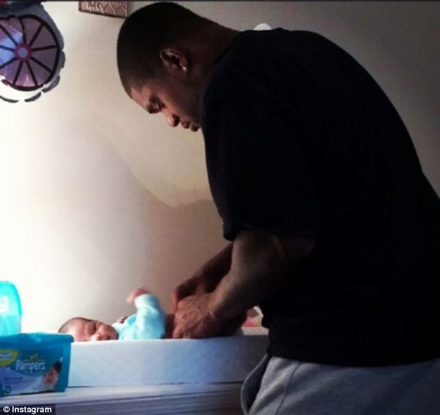 Jovan Belcher pictured changing his young child's diaper