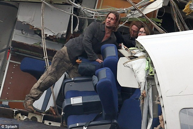 Crash and burn: Brad Pitt is left with a bloody face in plane crash scenes he filmed for World War Z in Berkshire, England a few days ago