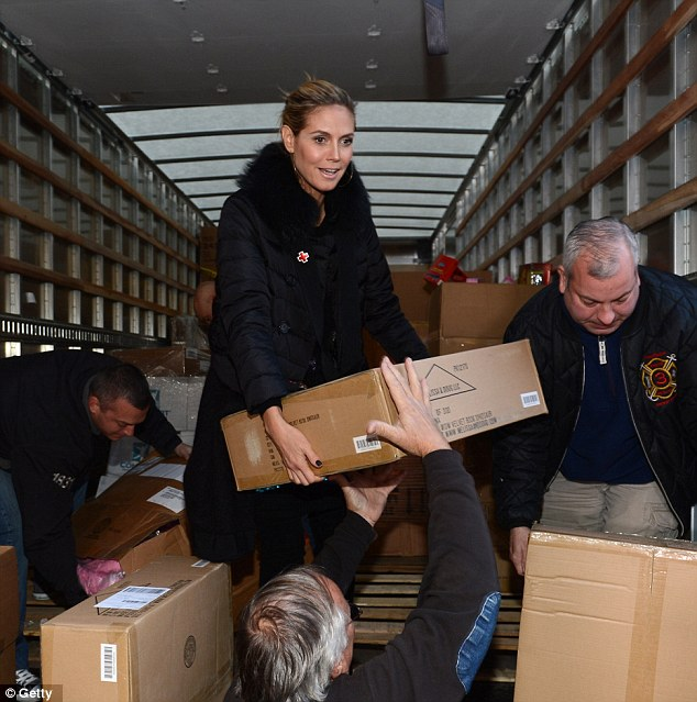 Putting her back into it: Heidi Klum seemed to be relishing helping with the aid effort in Seaford, New York on Sunday
