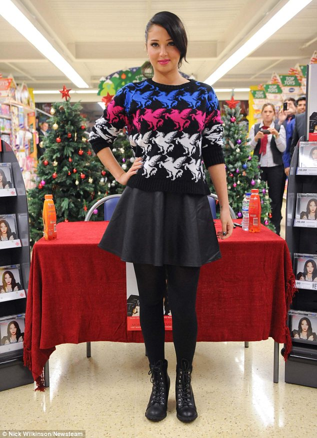 Low key: The singer paired her jumper with a simple leather skater skirt, opaque tights and lace up boots