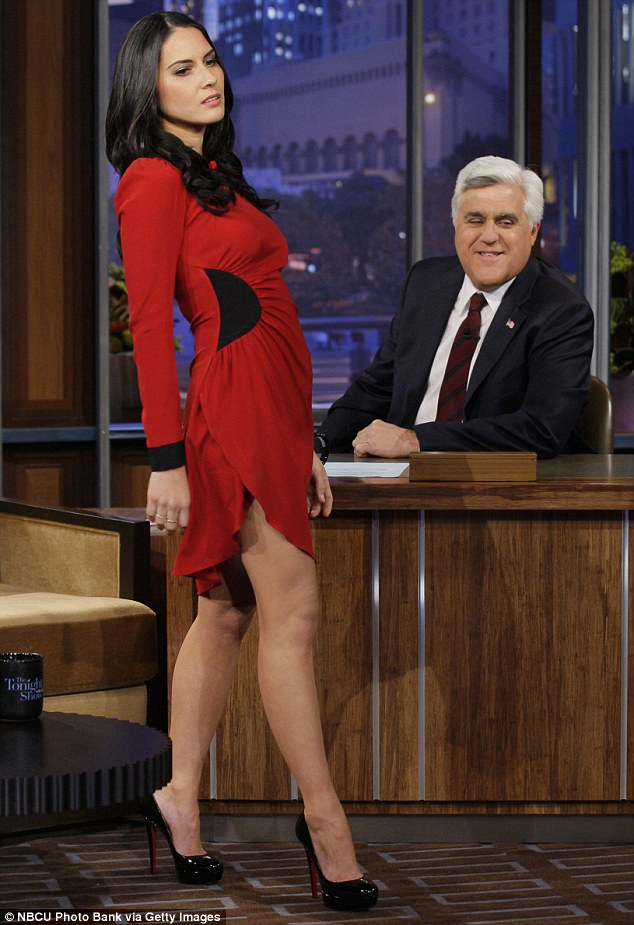 Strutting her stuff: Olivia Munn demonstrates her expert modelling skills in a fitted red mini dress on The Tonight Show with Jay Leno on Monday night