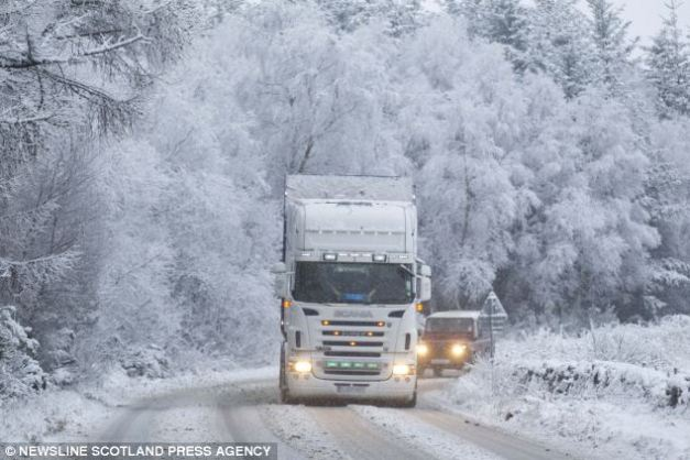 Festive scene: A flurry of snow hits the north-east of Scotland on the A957 in Aberdeenshire, with freezing conditions making driving hazardous across the country