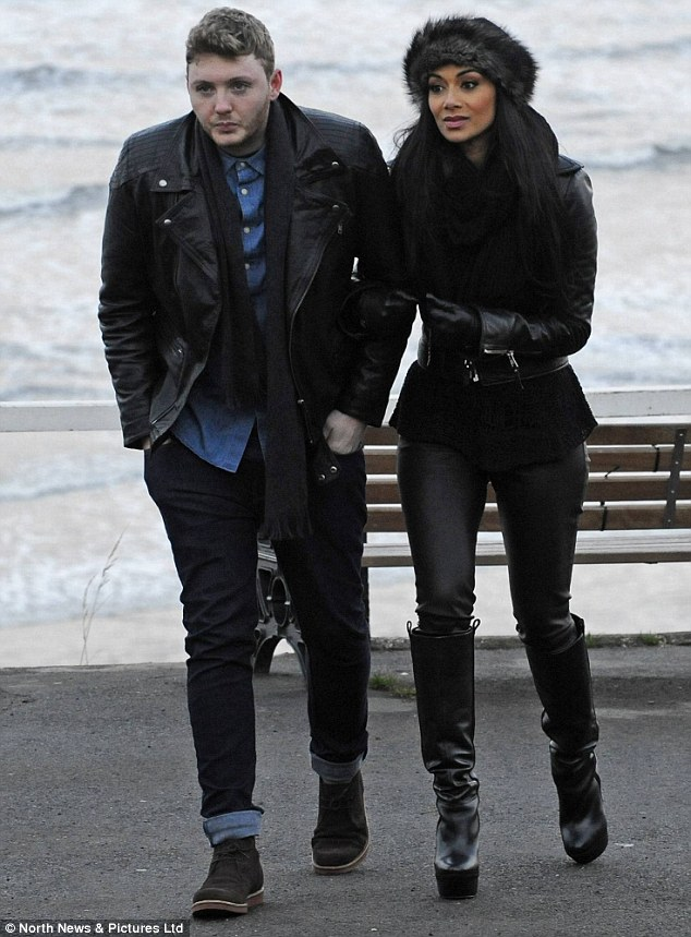 Walk this way: Nicole and James looked a little cold as they headed away from the rough sea