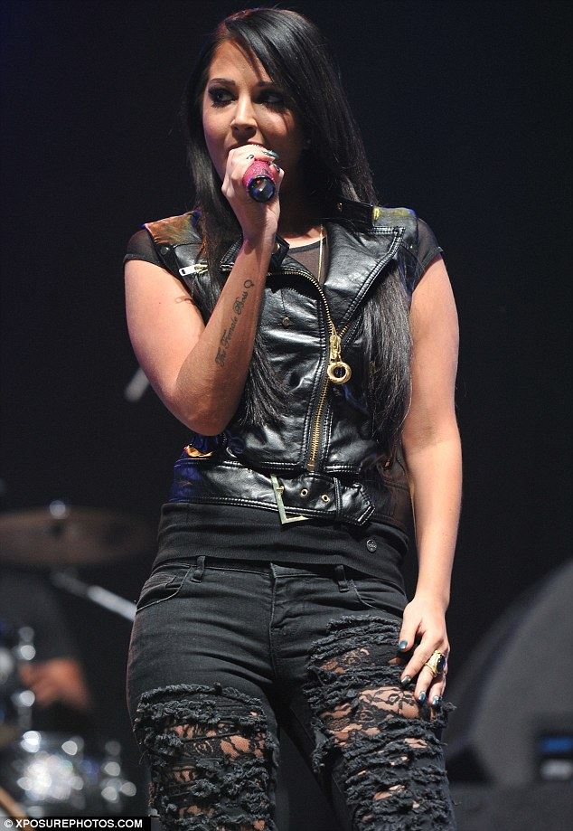 Trashy: The 24-year-old singer teamed a pair of unflattering ripped jeans with a cheap-looking plastic leather gilet