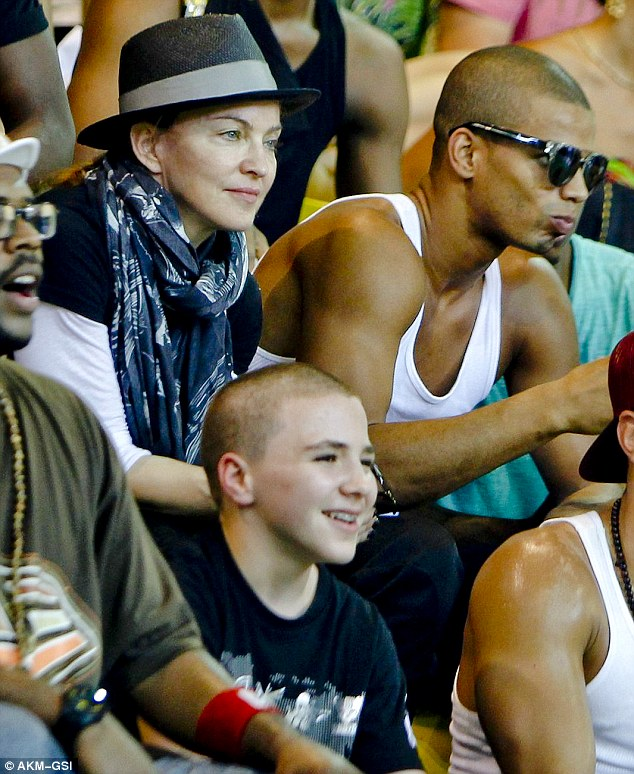 Madonna and her boys: The queen of pop, her boyfriend Brahim and son Rocco visited a shanty town in Brazil to take a look at how social projects are working