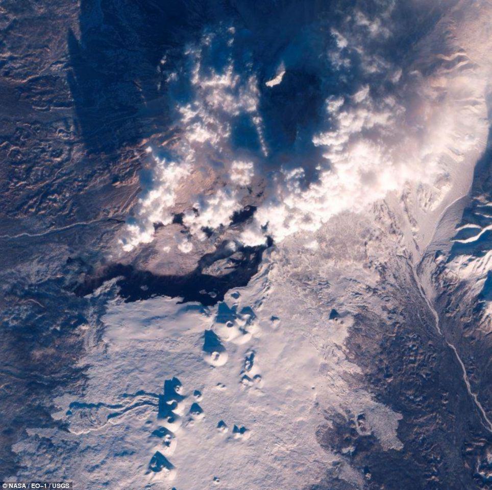 Eerie: En esta vista en luz visible desde el satélite de la NASA el flujo de lava es elegido como un río de oscuridad
