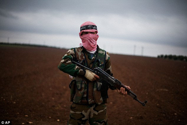 Assault: A Free Syrian Army fighter takes position close to a military base, near Azaz, which is now believed to have fallen to rebel hands