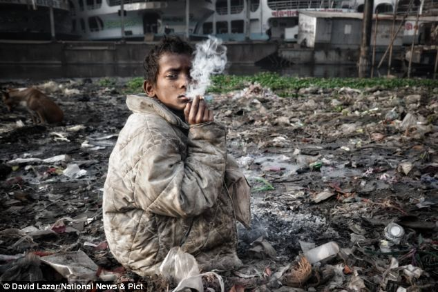 Innocence fading: The grinding poverty of a young boy smoking as he picks through rubbish to survive in Bangladesh
