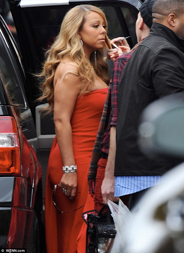 Getting ready for her close-up: A make-up artist was seen touching up Mariah's foundation before the taping
