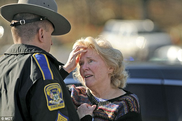 A woman talks to a state police officer for news about the 29 people believed to have been shot dead at the school