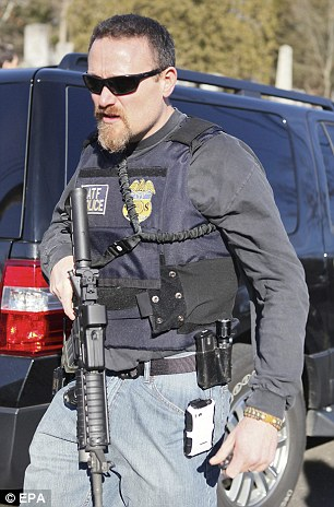 A member of the Connecticut State police leaves the scene outside the Sandy Hook Elementary School