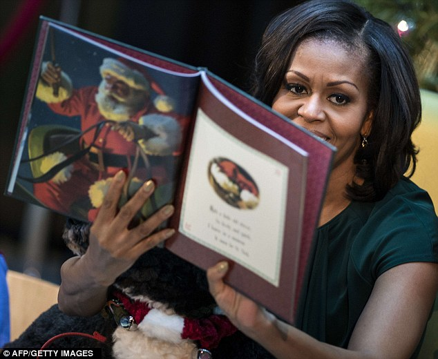 For all to see: Mrs Obama held up the book so the children could see the illustrations