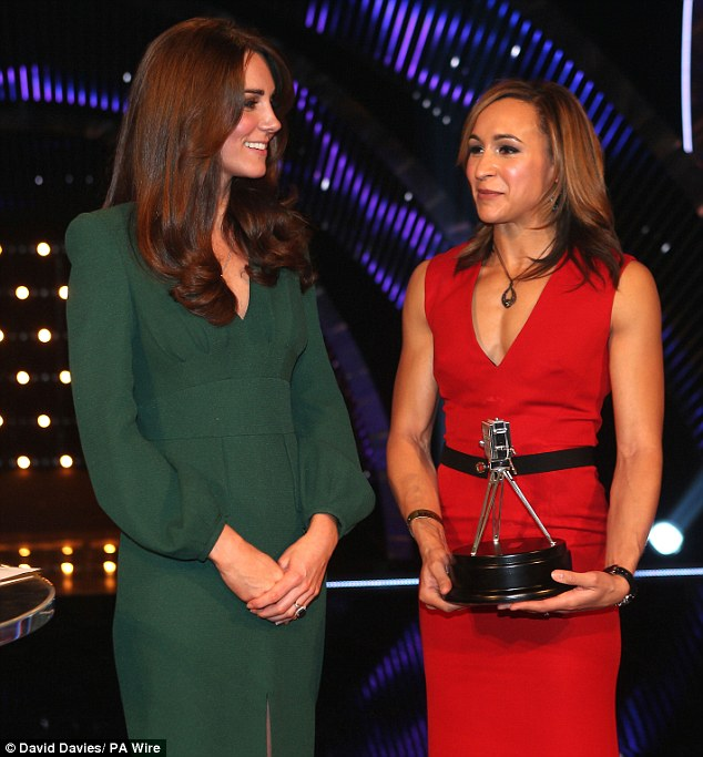 Festive: She smiled as she held her trophy while wearing her red frock, next to a radiant Kate in green