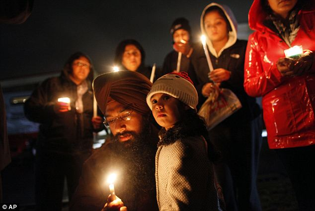 Pausing to reflect: A 3-year-old girl is accompanied by her father while lighting a candle outside of Newton High School while President Obama spoke at the memorial service