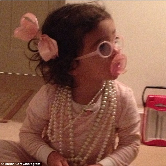 Pretty in pink: Mariah Carey tweeted a picture of her daughter Monroe enveloped in ropes of pearls on Monday with the caption: 'Ms. Monroe seems to think sometimes pearls can be your best friends too: )'