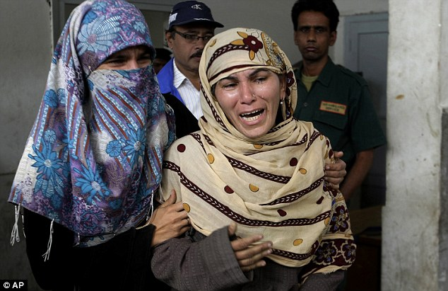 Rukhsana Bibi, center, is supported by a friend after visiting the body of her daughter, polio worker Madiha Bibi