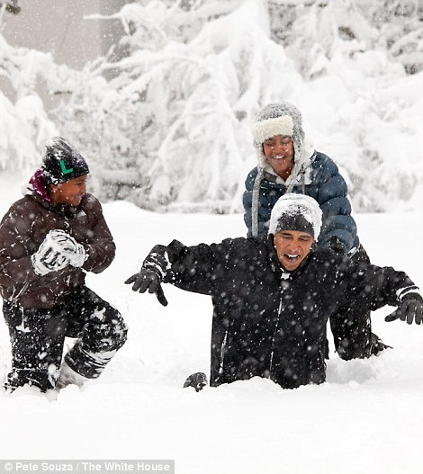 Obama plays with his daughters in the snow as Sasha, left, packs a snowball