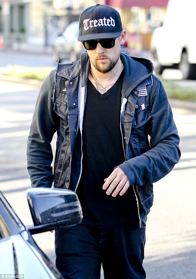 Too cool for school: Madden wore a fitted cap with a hooded jumper, sleeveless denim jacket, black top and jeans