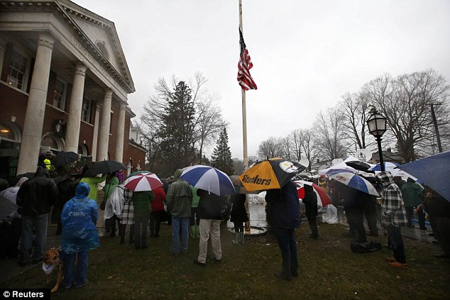 Rain: People stand in a driving rain outside the Edmond Town Hall during a moment of silence and ringing of church bells at 9:30am