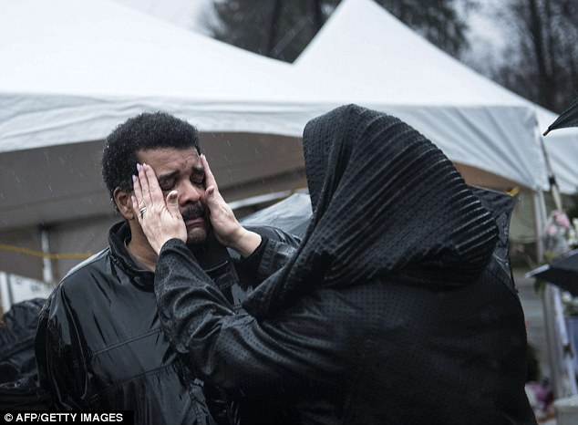 Too much: A woman wipes the face of a man after a moment of silence in Sandy Hook village December 21, 2012 in Newtown, Connecticut