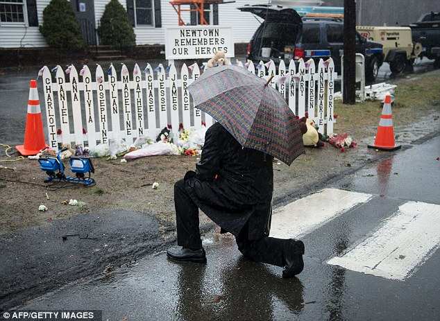 Names: A man kneels at a picket fence with the names of shooting victims during a moment of silence in Sandy Hook village