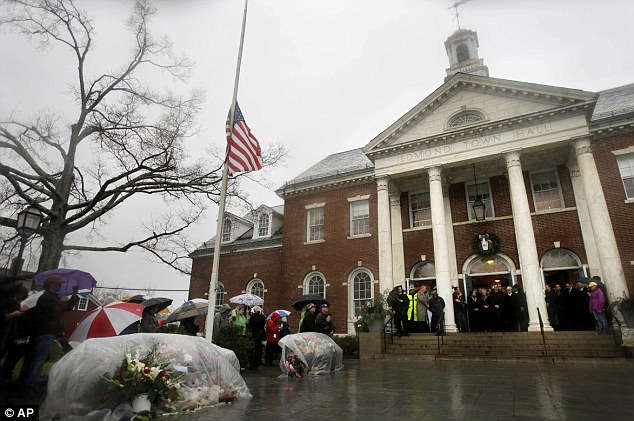 Remembering: Officials including Connecticut Governor Dan Malloy observe a moment of silence on the steps of Edmond Town Hall while bells ring 26 times in Newtown