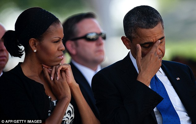 Tearful: President Obama appeared emotional as he sat next to First Lady Michelle Obama at the memorial service for the late Senator Daniel Inouye in Hawaii