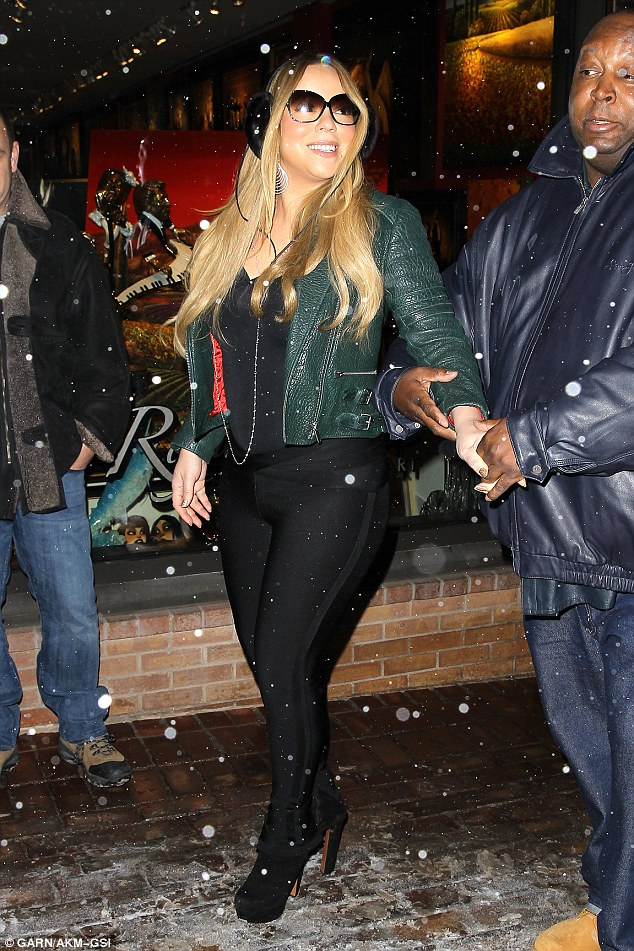 Timber! Mariah hangs on to her burly bodyguard as she steps across the icy walk in platform heels during a holiday shopping trip in Aspen, Colorado