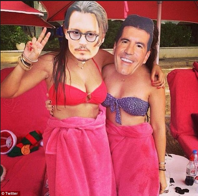 You are missed! Chloe posed behind a mask of her family friend, Simon Cowell, while her pal wore a mask of Johnny Depp