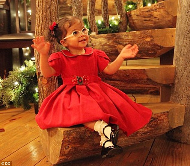Rustic cabin: Monroe also got glamourous in a classic red puffed-sleeve holiday dress with Peter Pan collar, matching pigtail bows, and white ruffled socks with black patent leather Mary Janes
