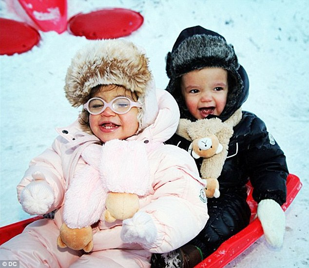 Adorable: The twins could not hide their delight as they sat together in a red sled