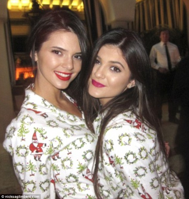 Family tradition: Kim's half-sisters Kendall and Kylie also stripped off their matching white Alexander McQueen dresses to change into the wreath-patterned PJs