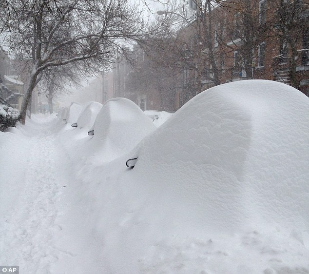 Eye spy: Parked cars hide under mounds of snow on Darling Street in Montreal after the city was hit with its first major blizzard of the winter