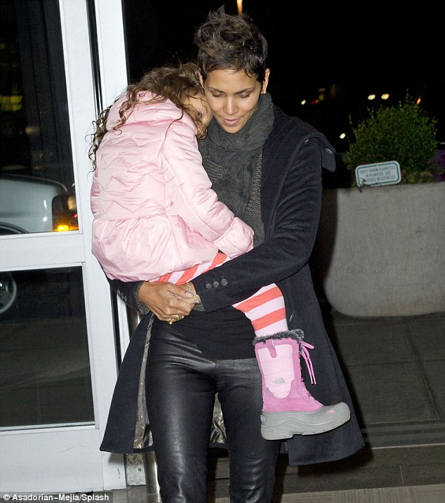 Fast asleep: Halle Berry reunites with her daughter Nahla after spending Christmas apart as they arrive at JFK airport in New York City on Friday