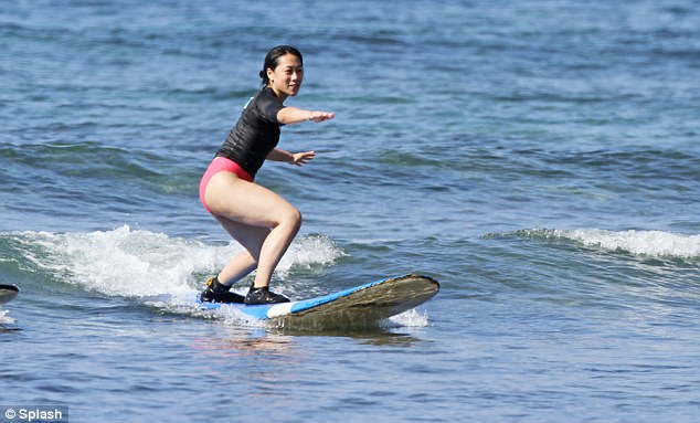 Crest of a wave: Priscilla Chan looks accomplished on a surfboard as she takes a break with husband Mark during their first Christmas as a married couple