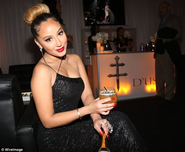 Enjoying the free bar: Adrienne Bailon sipped on a cocktail at the backstage bar Jay-Z had set up