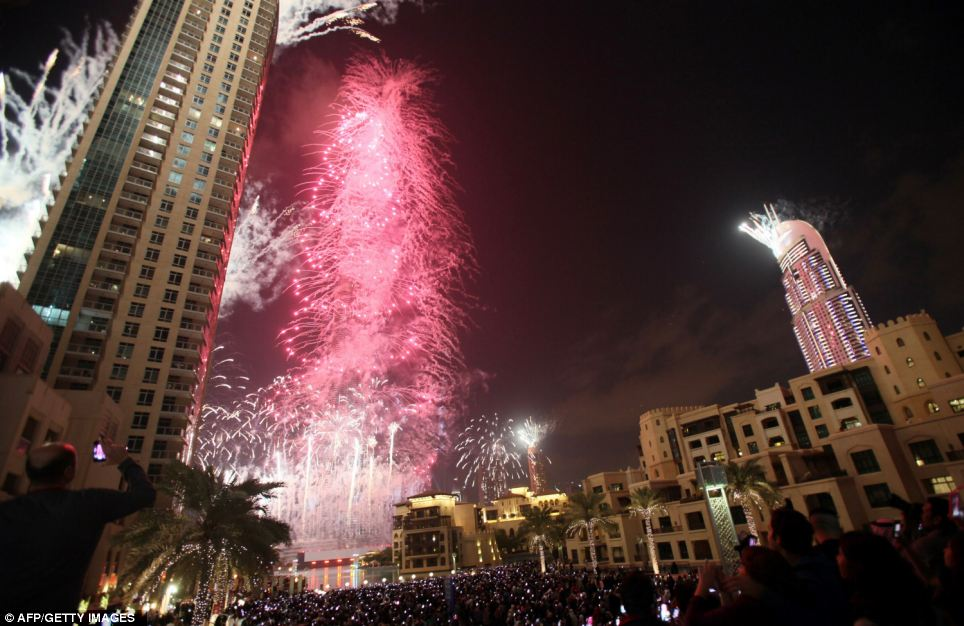 Fireworks illuminate Burj Khalifa while thousands of people gather to celebrate the New Year at midnight in Dubai