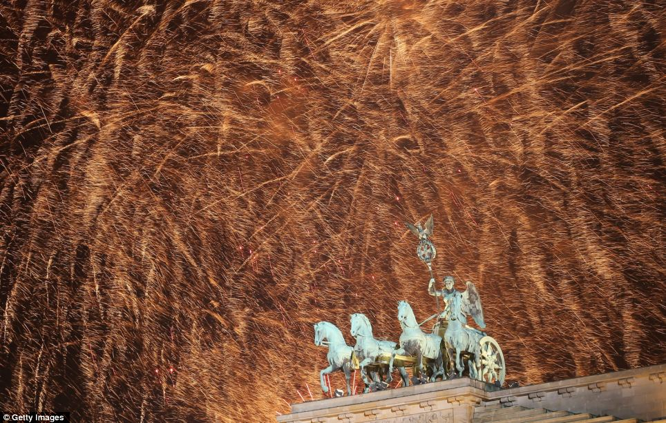 An amazing spectacle of fireworks lights up the sky behind the Quadriga statue on top of the Brandenburg Gate shortly after midnight on January 1, 2013 in Berlin, Germany