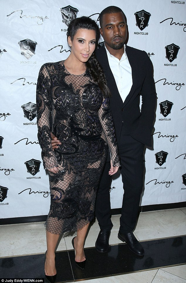 Covering up: Kim Kardashian hides her pregnant figure underneath lace detailing on her sheer dress as she hosts a Las Vegas New Year's Eve party with Kanye West