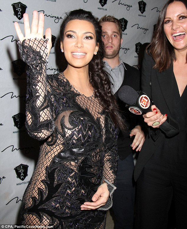 Protective hand: Kim keeps a hand cupped on her stomach as she chats to press
