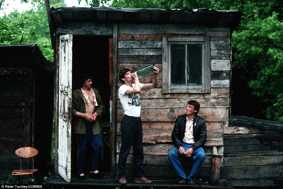 Taking their minds off things: Siberian men relax outside a shack in the town of Novokuznetsk, which was hit hard by widespread economic problems in the early 90s