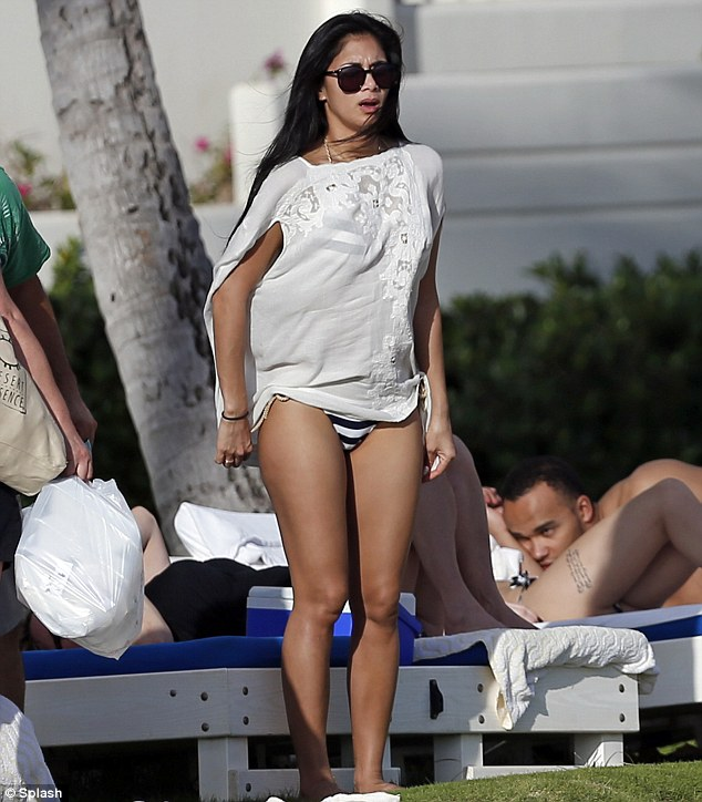 Chillaxing: Nicole Scherzinger covers up in a white tunic as she spends a day at the beach in Hawaii with boyfriend Lewis Hamilton's family, including his brother Nicolas (far right)