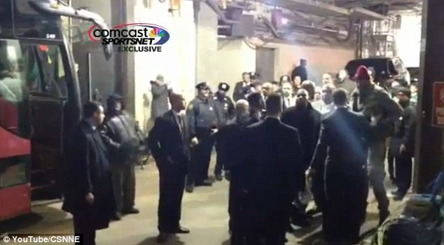 Taking it outside: Carmelo Anthony, pictured right in a red hat, is confronted by security as he waits for Kevin Garnett outside the Celtics team bus
