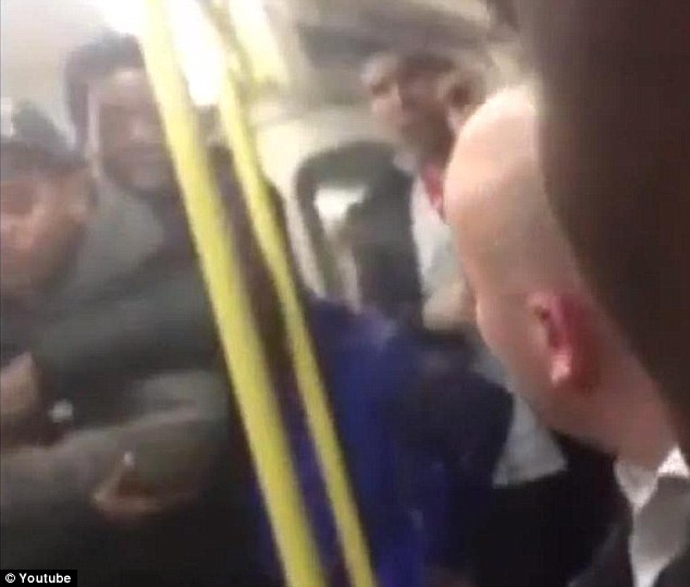 Furious reaction: The 19-year-old is dragged away from the woman and told to 'relax' by fellow passengers, while the driver asks what is going on over the intercom