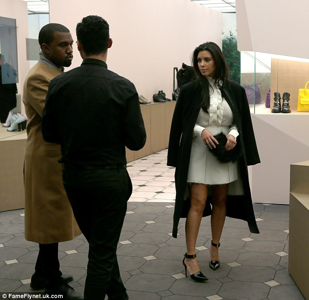 Talking shop: Kim watched and listened on as Kanye talked to the shop assistant