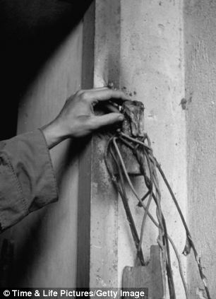 Unident hand touching destroyed hinge of door to Adolf Hitler's command bunker, burned off by advancing Russian combat engineers.