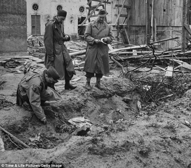 Examination: LIFE correspondent Percy Knauth sifting through the dirt & debris in the shallow shell hole where the bodies of Hitler and Eva Braun were thought to have been burned after their suicides, in the garden of the Reichstag