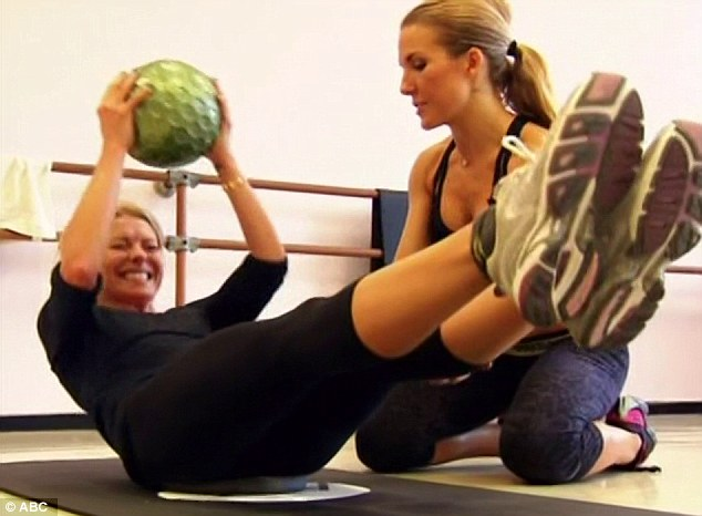 Crunch time: Kelly had a pained look on her face as she did crunches with a heavy ball