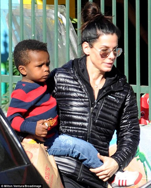 He's not heavy, he's my son: Sandra Bullock carries Louis Bardo in Los Angeles, California, on Wednesday